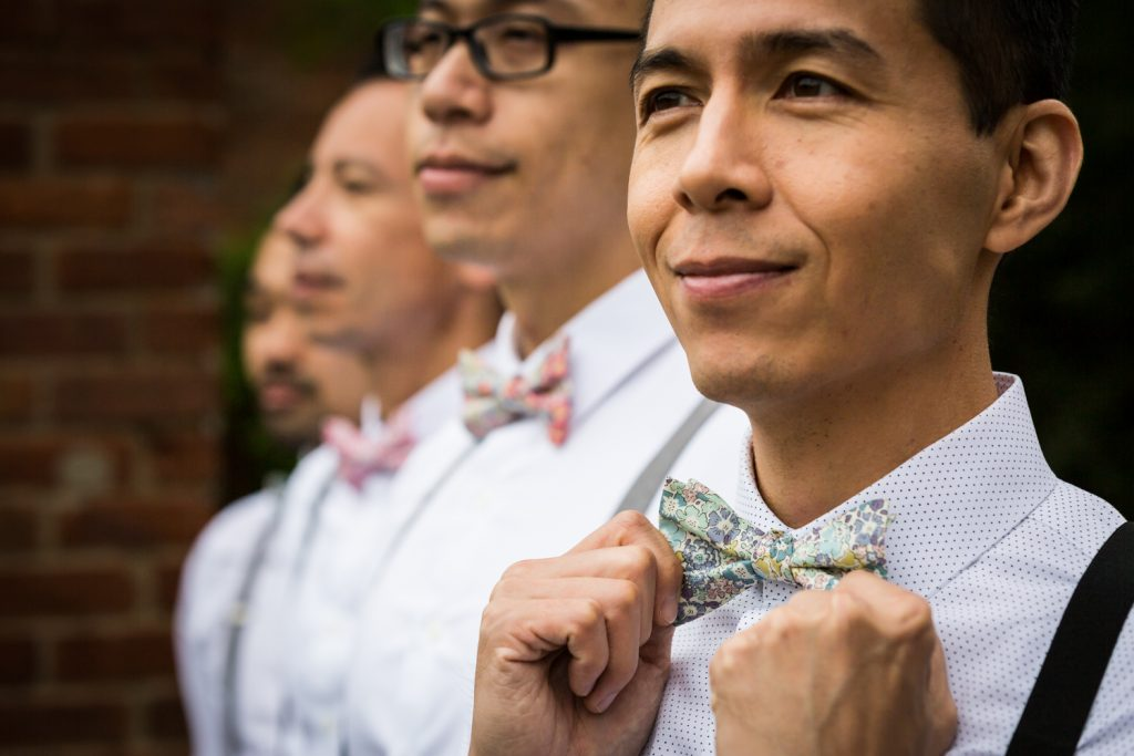 Groom holding bow tie with groomsmen in background