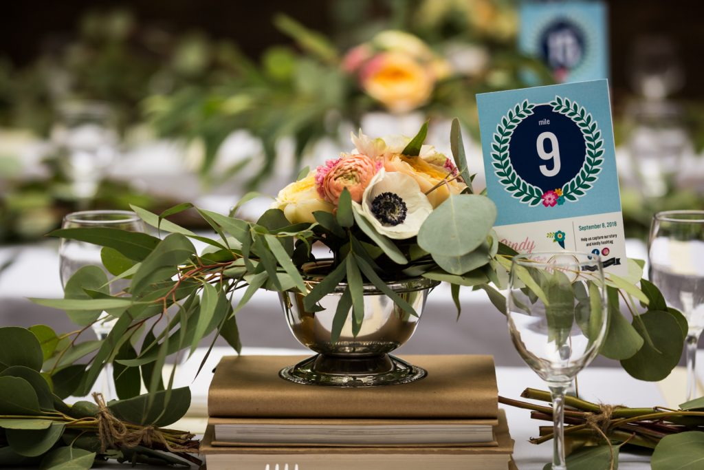 Floral centerpiece on stack of books for an article on the pros and cons of a restaurant wedding