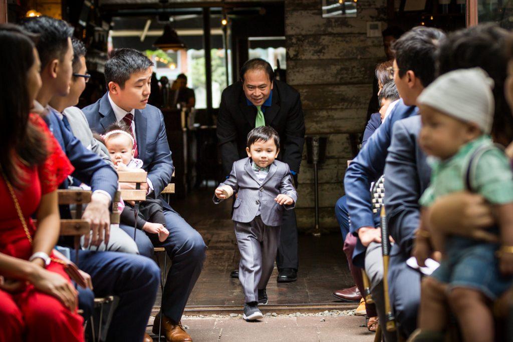 Little ring bearer running down aisle during wedding ceremony