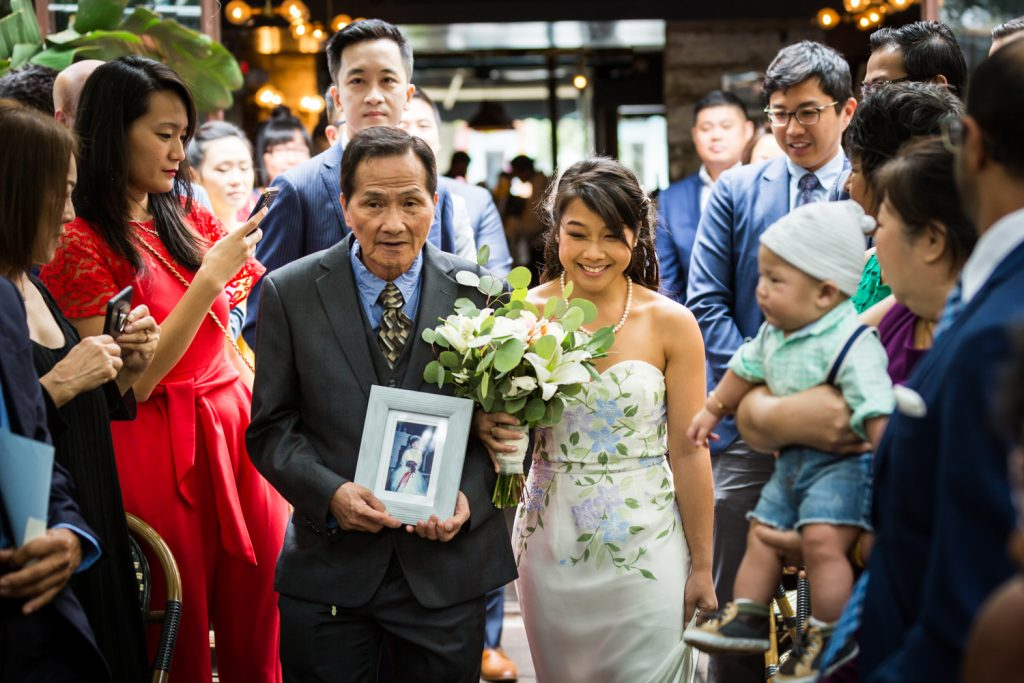 Bride and father walking down aisle with photo of mother at restaurant wedding ceremony