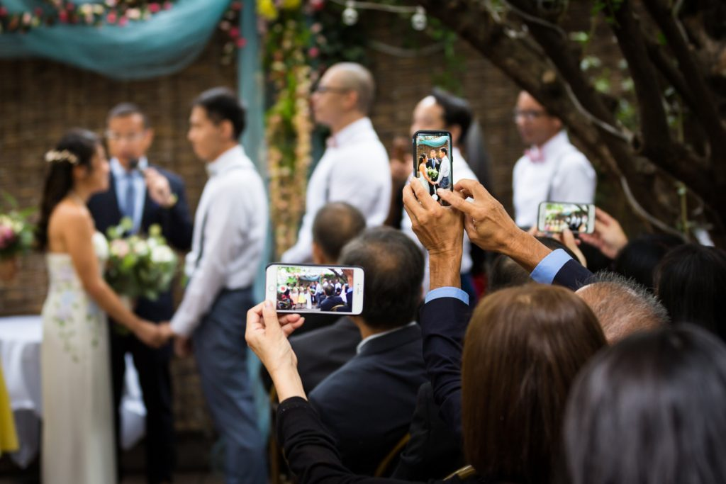Guests taking photos of wedding ceremony with cell phones