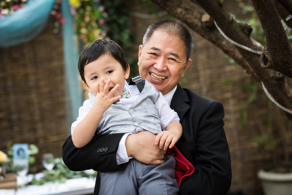 Grandfather holding up grandson for an article on the pros and cons of a restaurant wedding