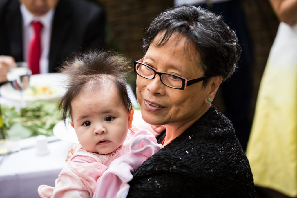 Grandmother holding baby girl for an article on the pros and cons of a restaurant wedding