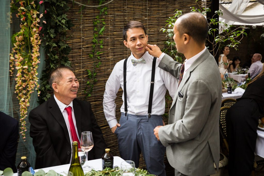 Guest pinching groom on the cheek for an article on the pros and cons of a restaurant wedding