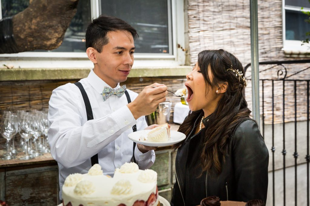 Groom feeding bride cake for an article on the pros and cons of a restaurant wedding