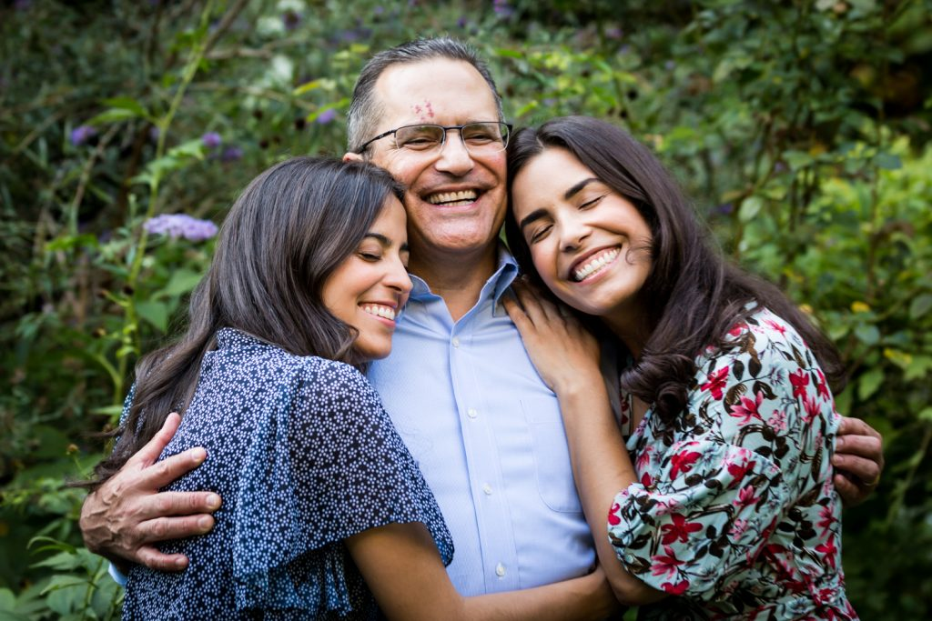 Father and two women hugging in middle of garden at a community garden family portrait session