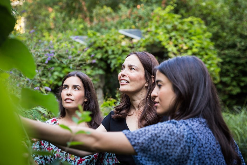 Woman showing plants to two daughters in middle of garden