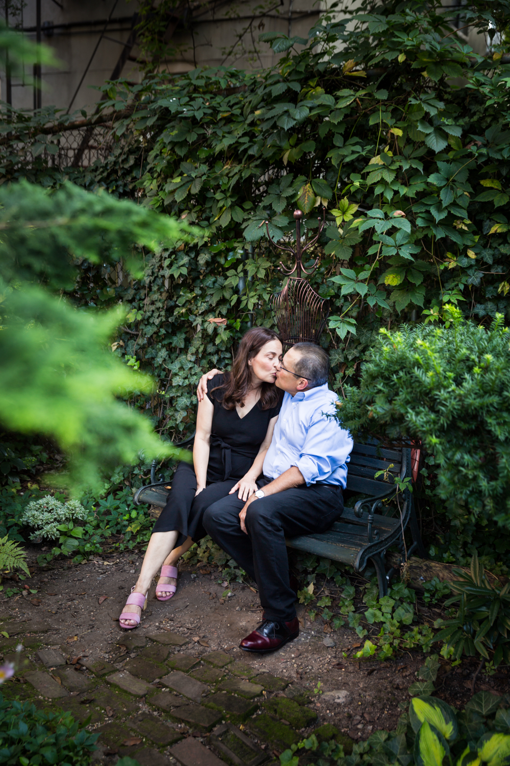 Older couple kissing in middle of garden at a community garden family portrait session