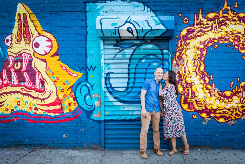 Couple kissing against colorful mural in East Village