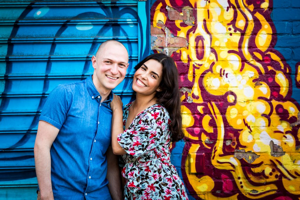 Couple standing against colorful mural in East Village