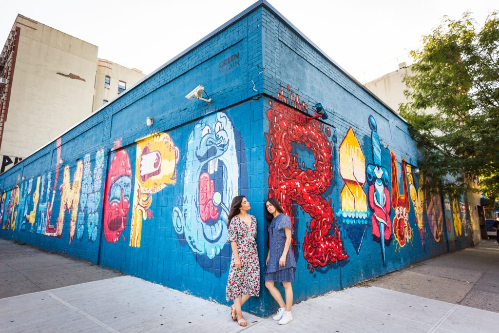 Two sisters standing against corner of colorful mural in East Village