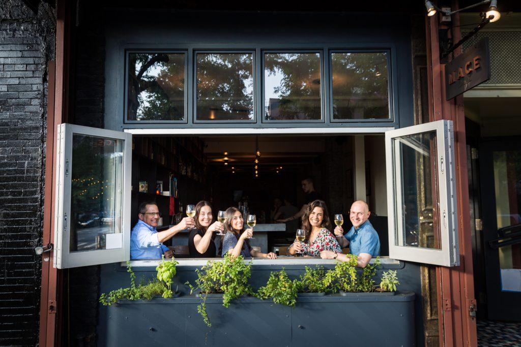 Family raising glasses of wine through window of wine bar