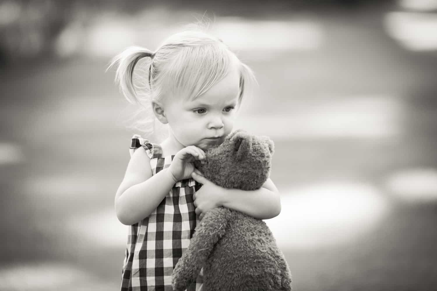 Black and white photo of little girl holding stuffed teddy bear
