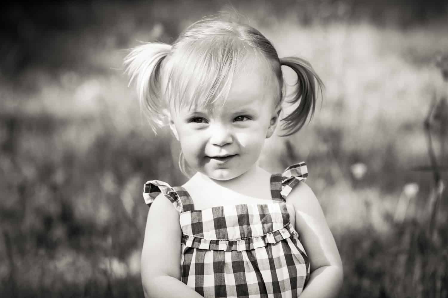 Black and white photo of little girl wearing checked dress