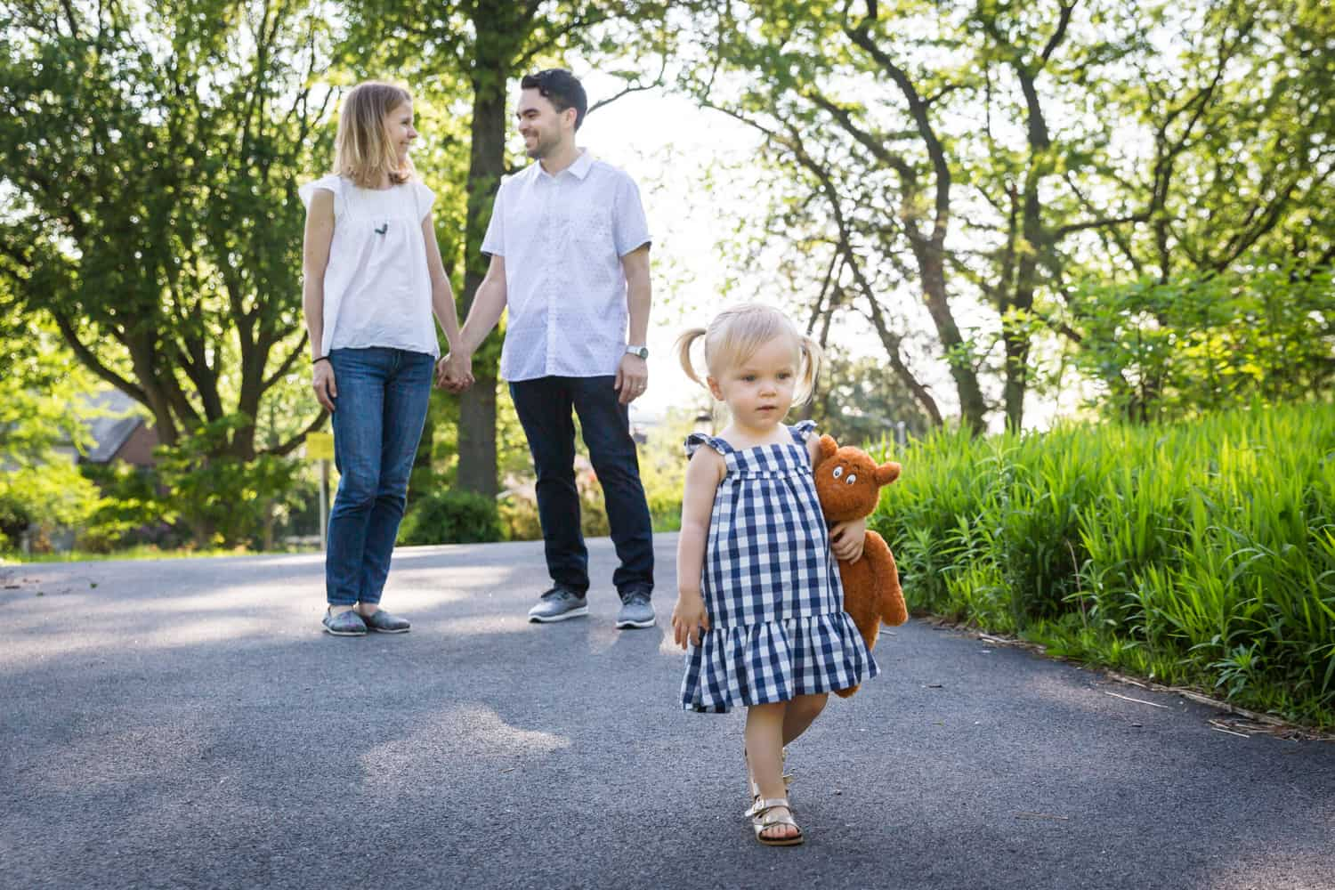 Parents holding hands behind little girl wearing blue checked dress