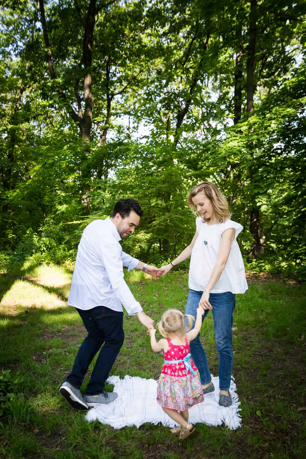 Parents and little girl playing merry-go-round during a Forest Park family photo shoot