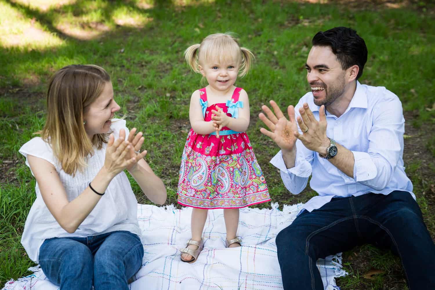 Parents clapping with little girl on blanket during a Forest Park family photo shoot