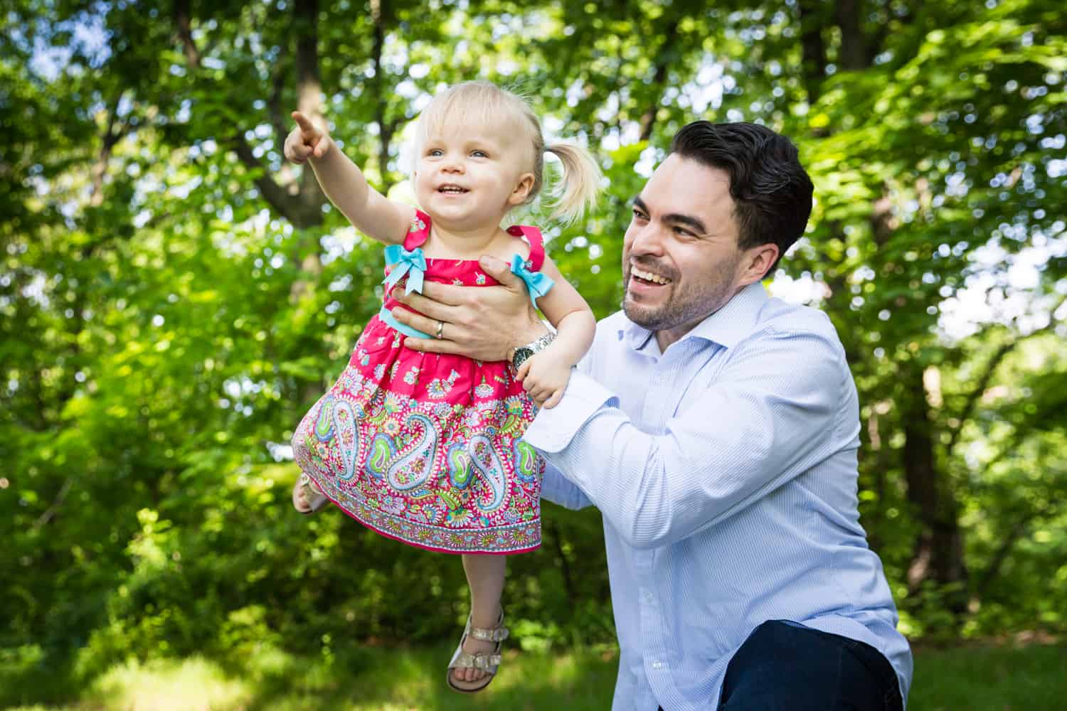 Father playing airplane with little girl during a Forest Park family photo shoot