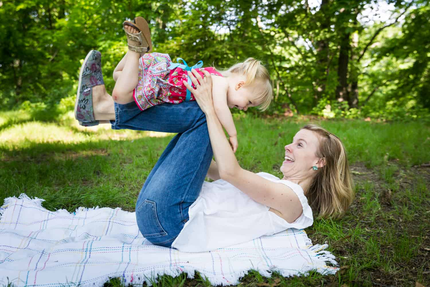 Mother lifting little girl on her knees during a Forest Park family photo shoot