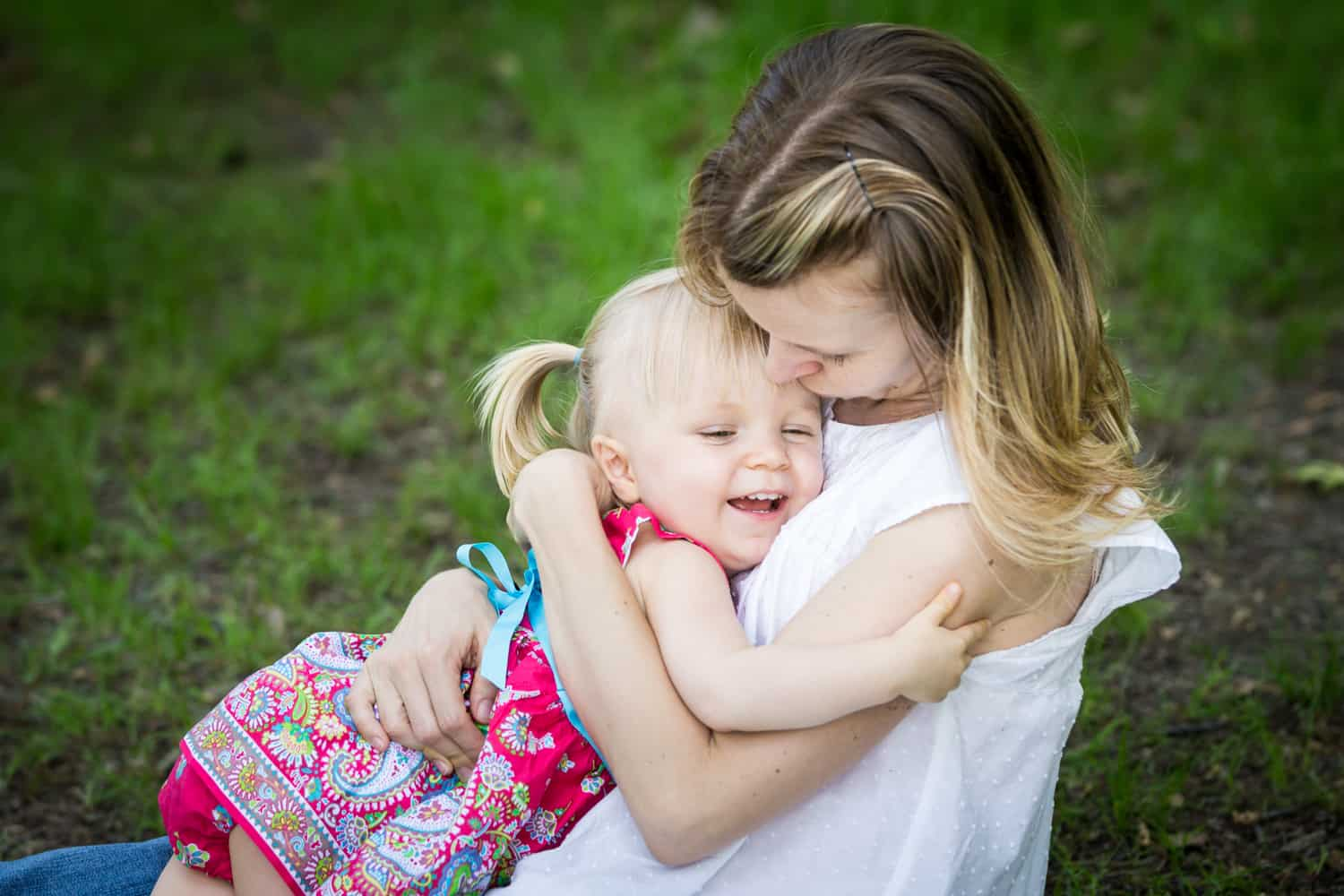Mother hugging little girl with pigtails during a Forest Park family photo shoot