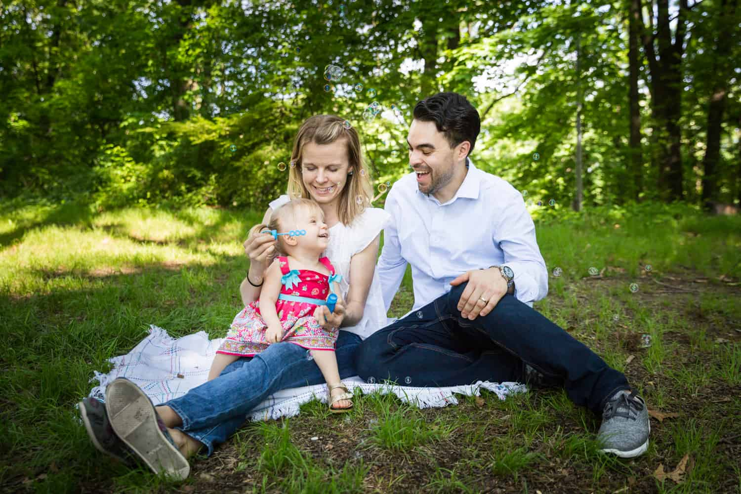 Parents and little girl blowing bubbles on blanket during a Forest Park family photo shoot