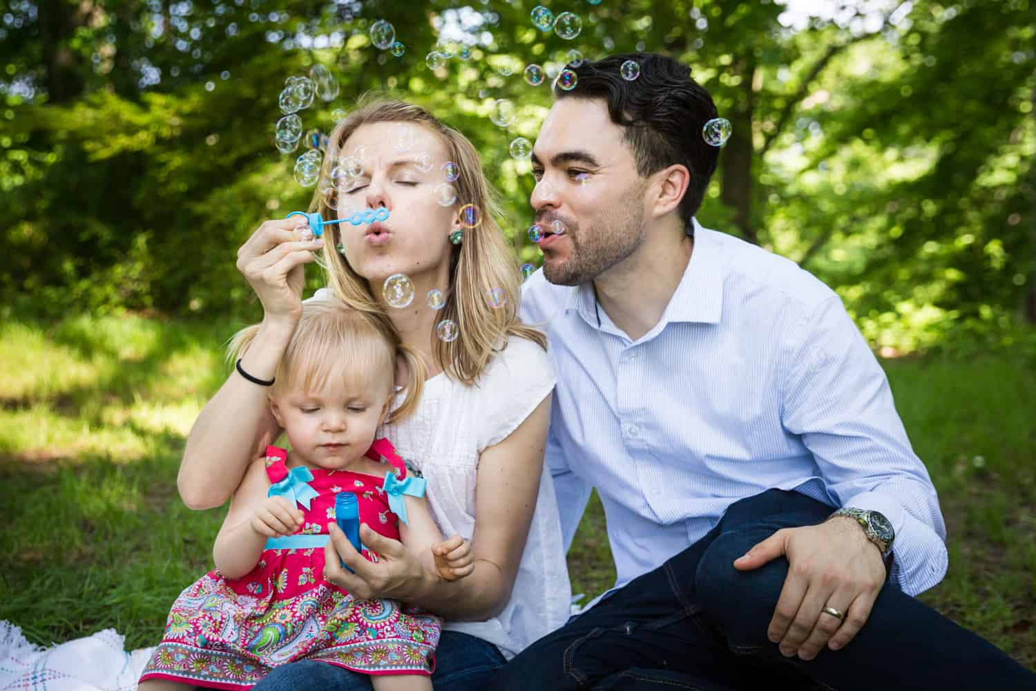 Parents and little girl blowing bubbles during a Forest Park family photo shoot