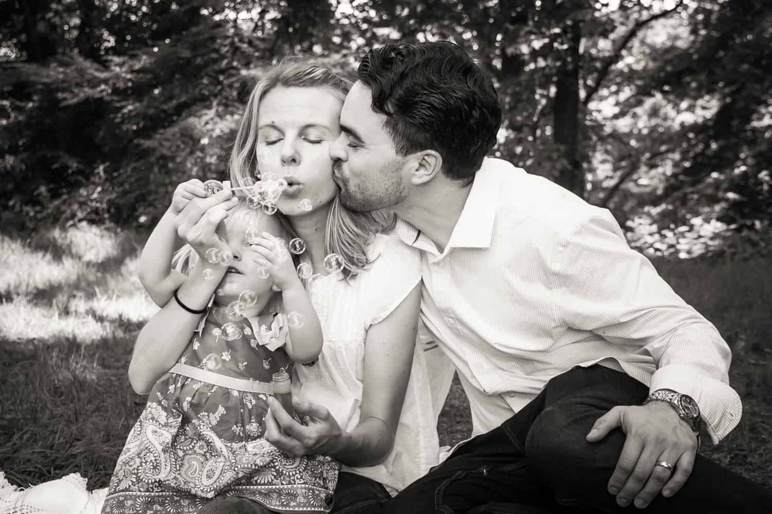 Black and white photo of father kissing mother on the cheek blowing bubbles with little girl