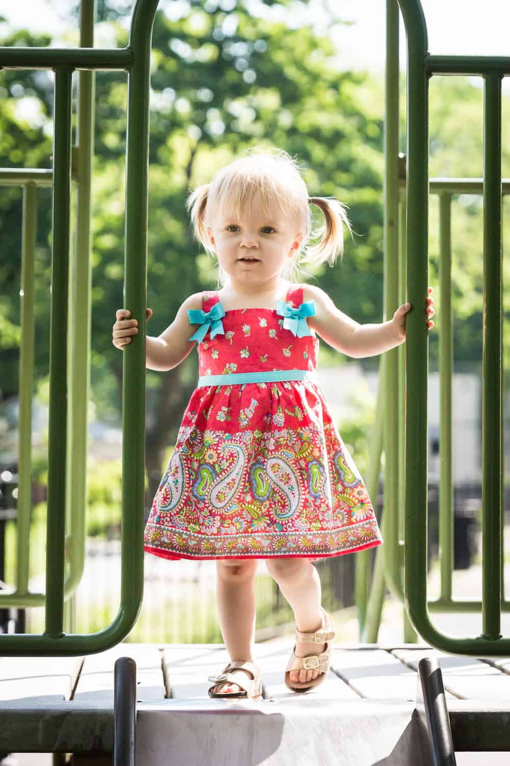 Little girl standing on slide in sunlight during a Forest Park family photo shoot