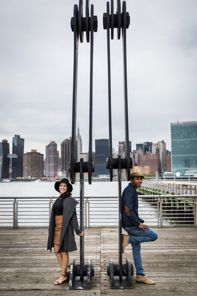 Couple standing beside dock equipment in Long Island City engagement shoot