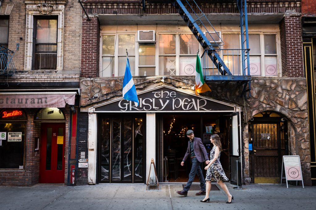 Couple walking past Grisley Pear for a Greenwich Village engagement portrait