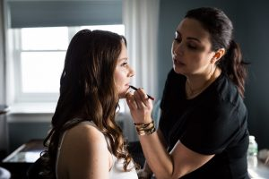 Bride applying lipstick at a Larchmont Shore Club wedding