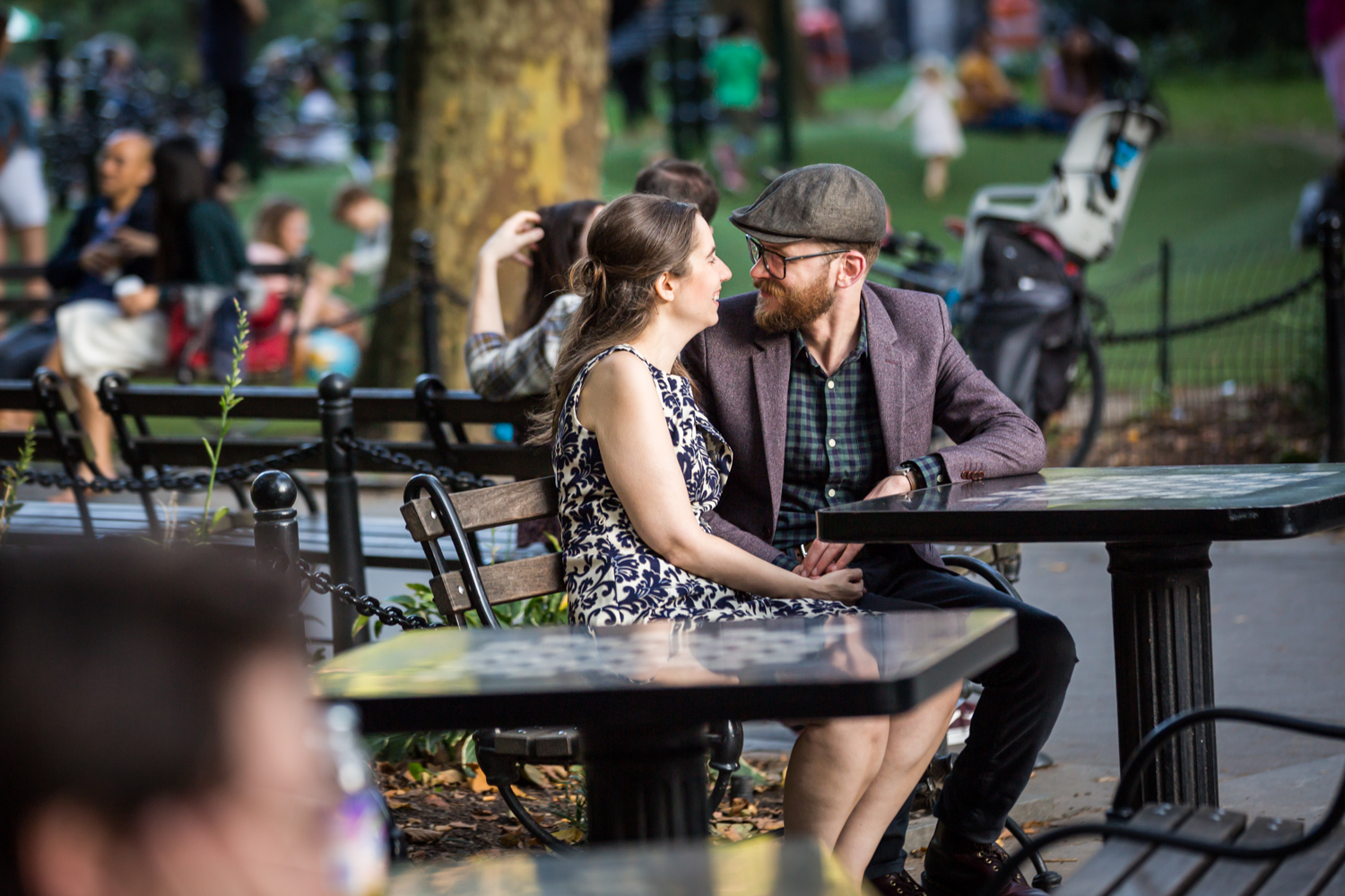 Couple sitting at chess table in Washington Square Park for a Greenwich Village engagement portrait