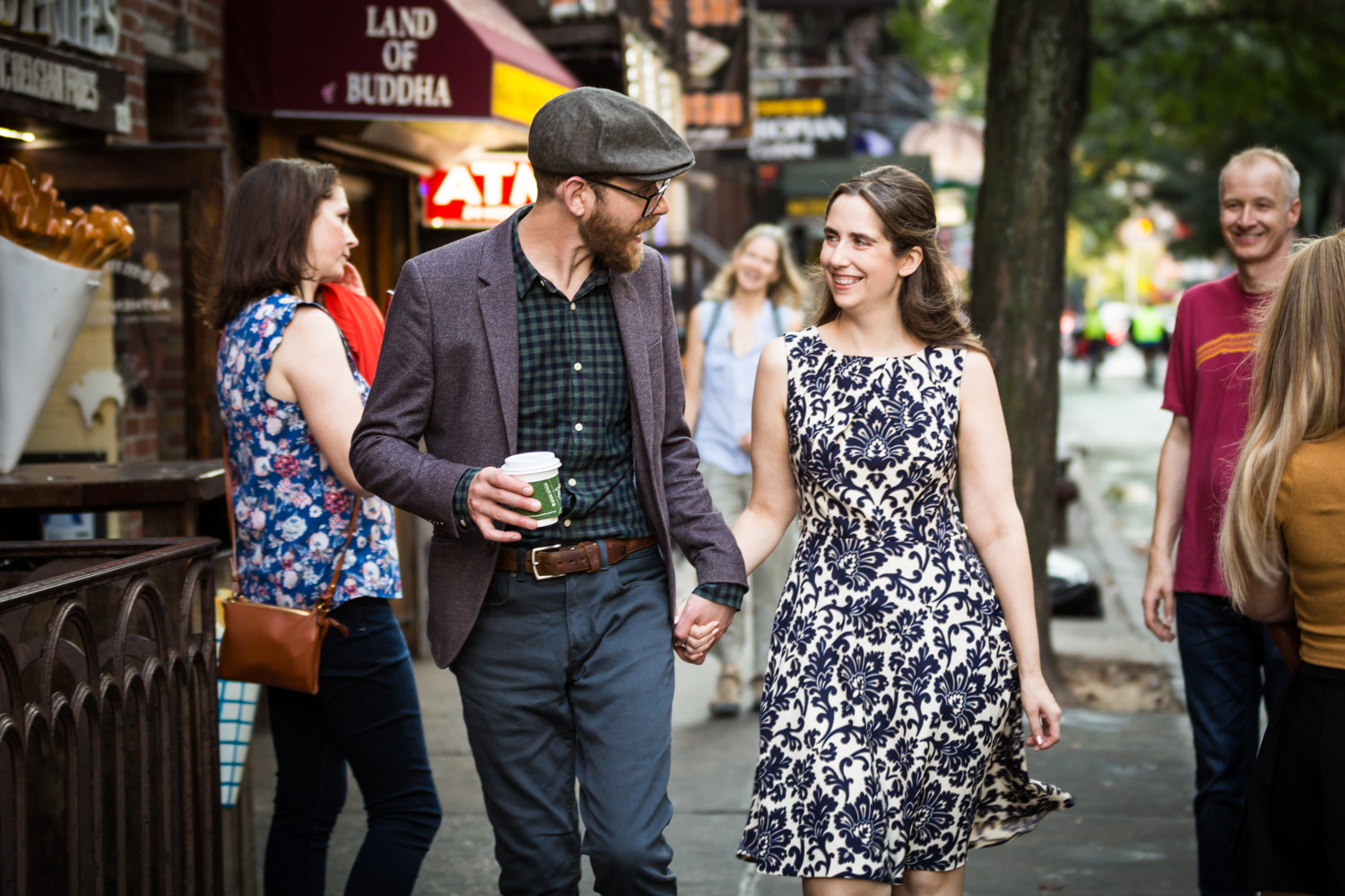 Couple holding hands and walking on MacDouglas Street for a Greenwich Village engagement portrait