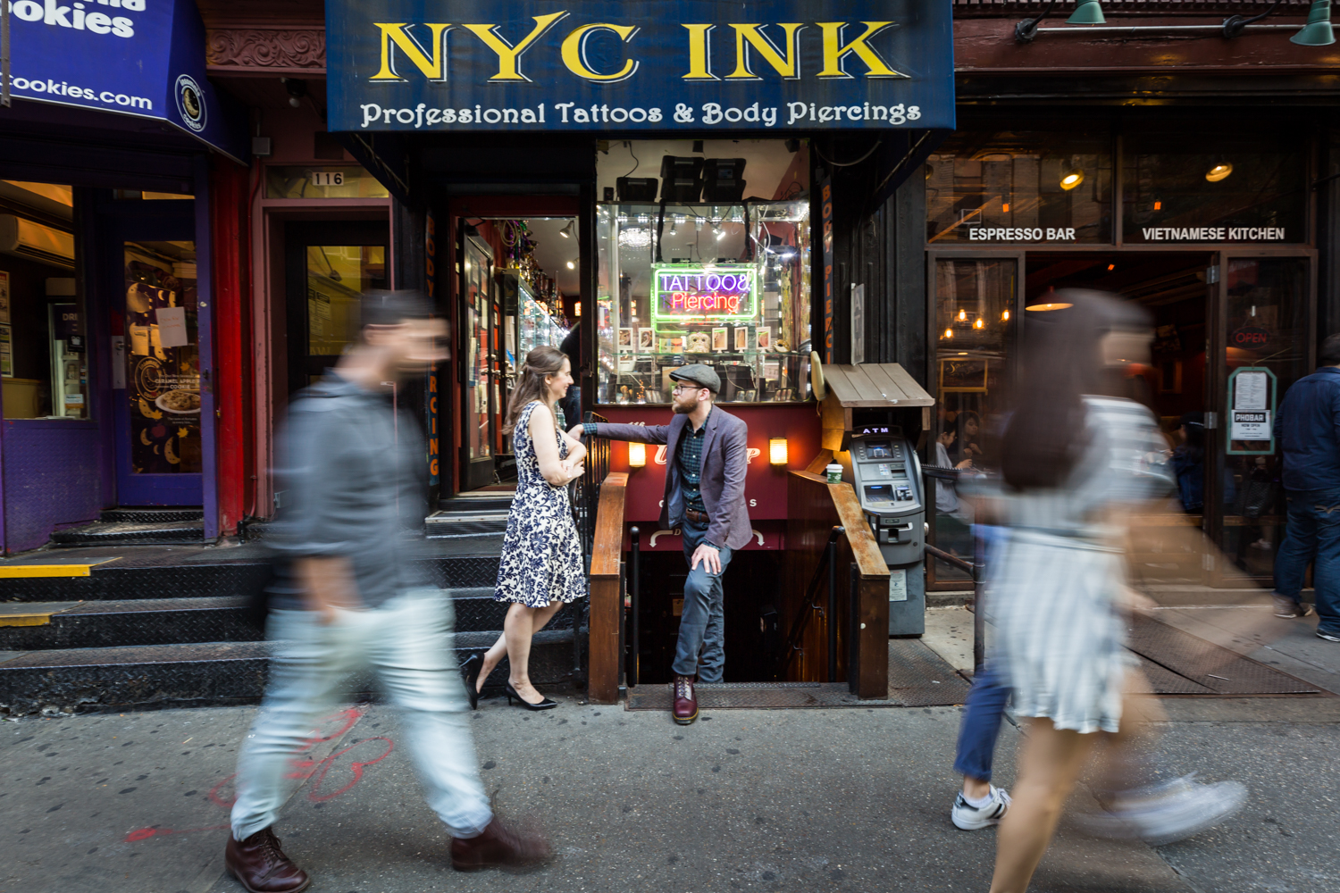 Couple in front of tattoo shop with people walking past in a blur for a Greenwich Village engagement portrait