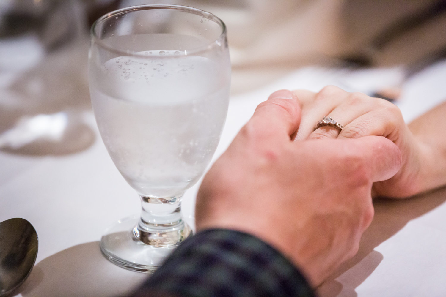 Close up on couple holding hands at table with woman wearing engagement ring