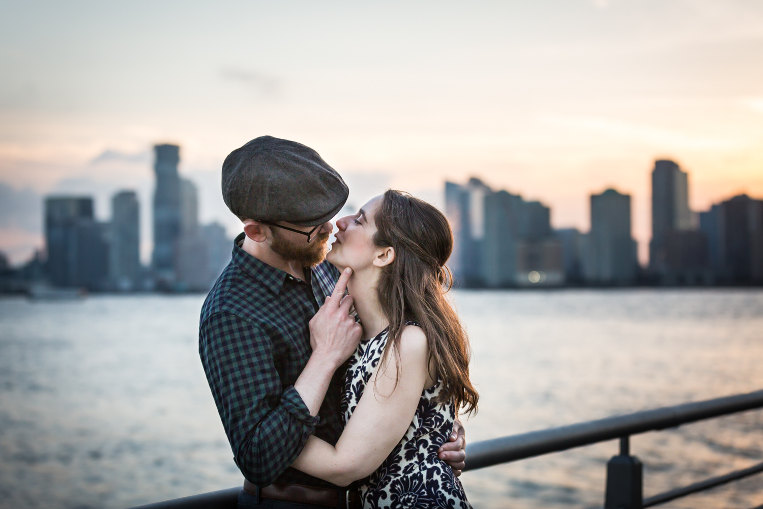 Man lifting up woman's head with his finger in front of Hudson River