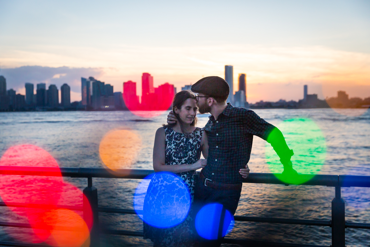 Man kissing woman's head with colored lights in front of Hudson River