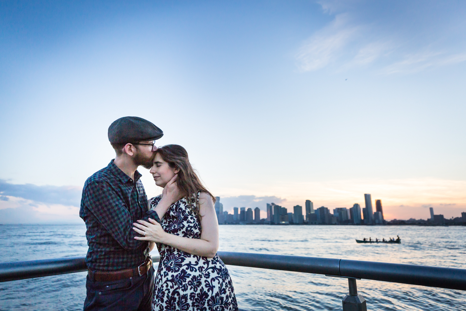 Man kissing woman's head in front of Hudson River