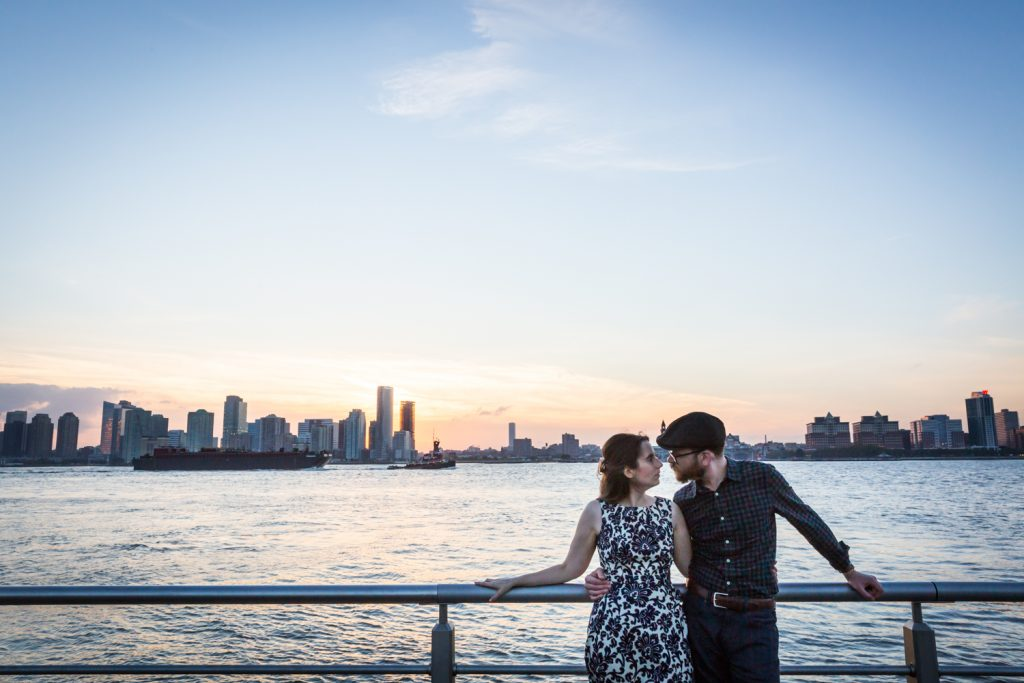 Couple leaning against railing with Hudson River at sunset in background