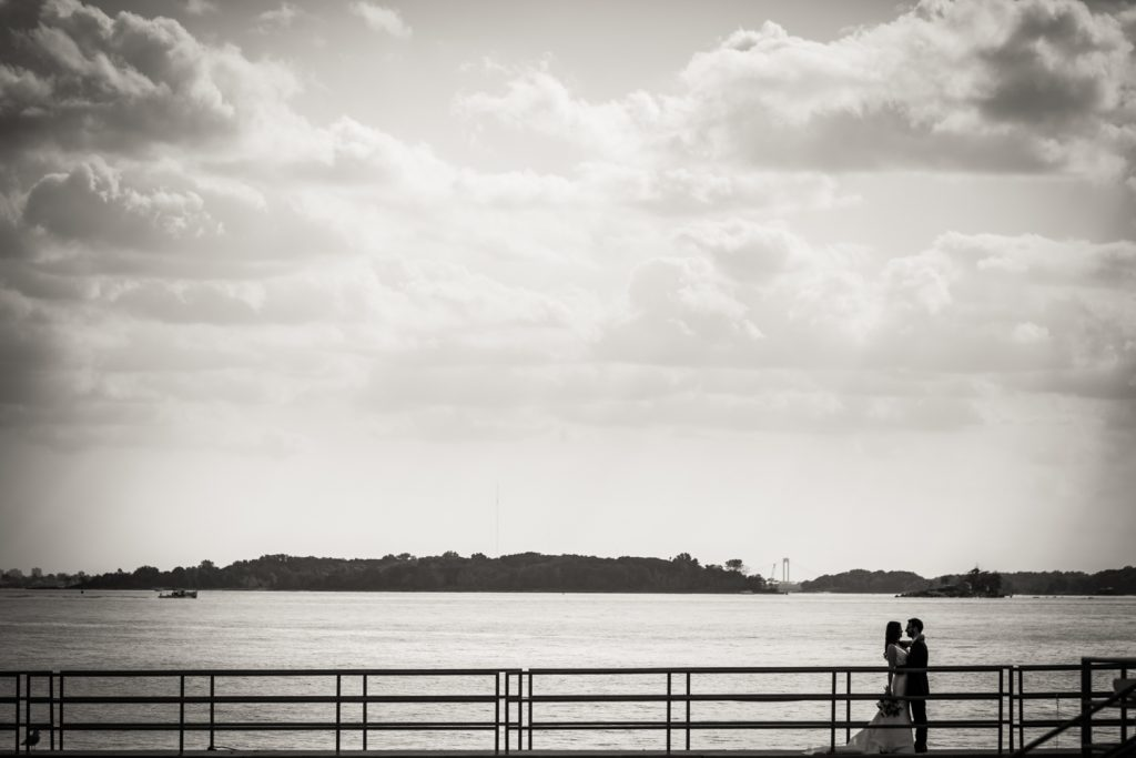 Black and white photo of bride and groom hugging on dock