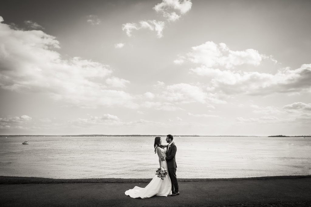 Black and white photo of bride and groom in front of water