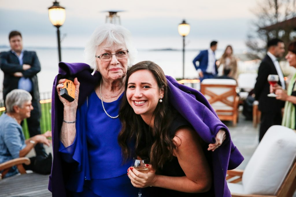 Older woman and younger woman under one purple coat at cocktail hour