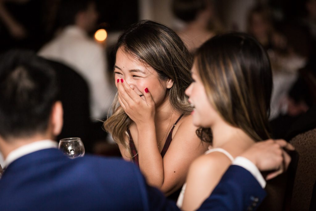 Female guest laughing during wedding reception