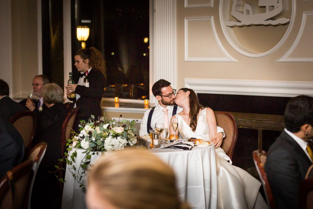 Bride kissing groom at sweetheart table