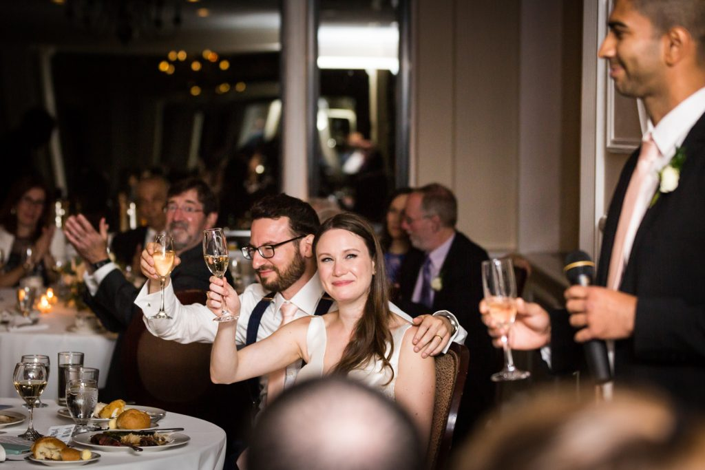 Bride and groom raising champagne glasses during toast at a Larchmont Shore Club wedding