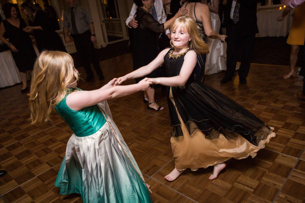 Two little girls dancing barefoot at Larchmont Shore Club wedding reception