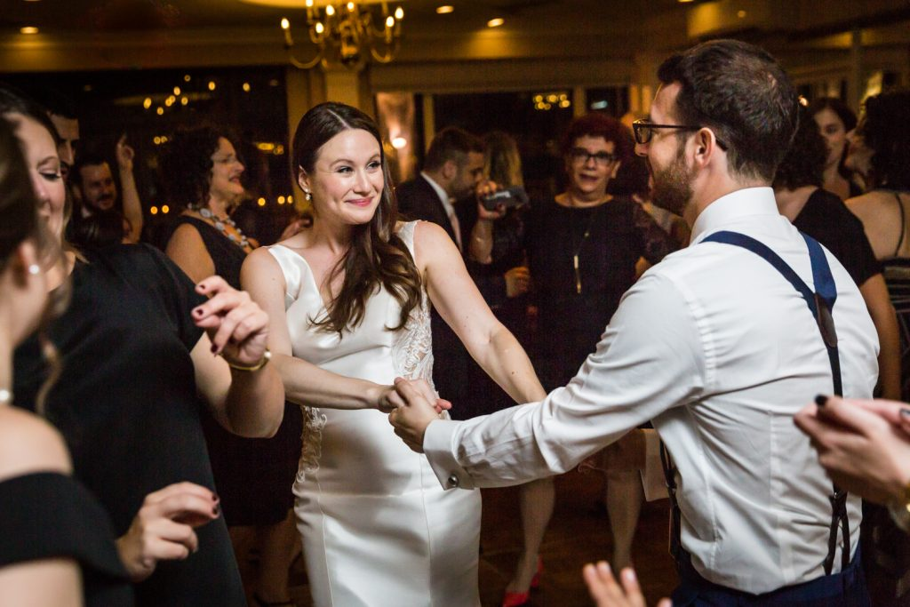 Bride and groom holding hands and dancing at Larchmont Shore Club wedding reception