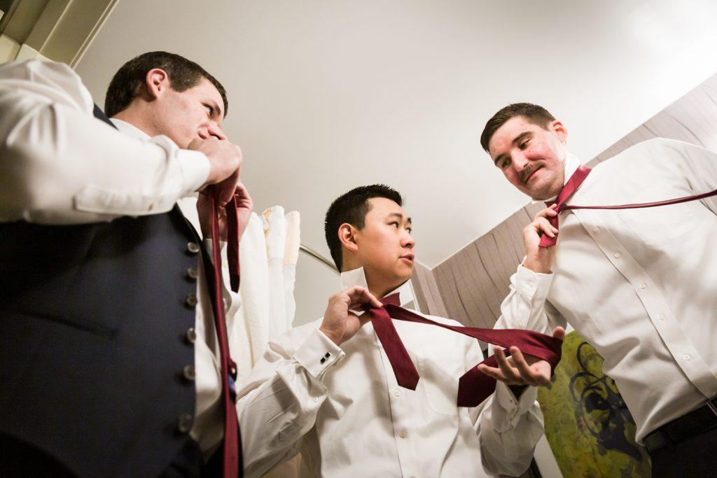Groom and groomsmen putting on ties at a Westbury Manor wedding