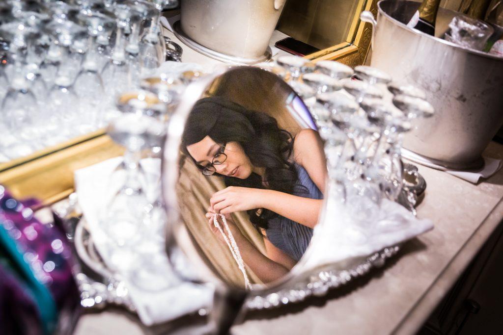 Reflection in mirror of bridesmaid looking at necklace at a Westbury Manor wedding