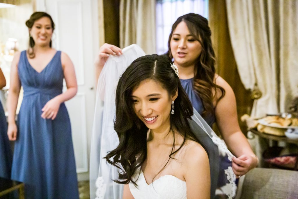 Bridesmaid attaching veil to bride's hair at a Westbury Manor wedding